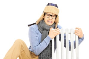 Chilled young man with winter hat sitting next to a radiator isolated on white background